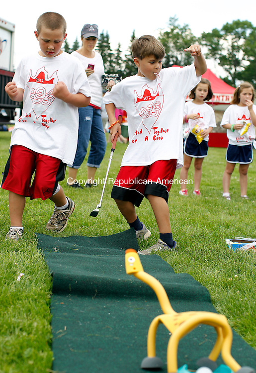 """Cheshire, CT-08 June 2012-060812CM04-  Benjamin Wable, 8, (center) celebrates with his brother,  Jack, 7 , both of Cheshire after sinking a put during a game at a """"Kids Care"""" event during the 16th annual American Cancer Society Relay for Life of Cheshire Friday afternoon at the Cheshire High School.  The kids care event kicked off 2 hours before the relay.  It featured Cheshire elementary school students making crafts, selling snacks and working at different games.  The proceeds will go to the American Cancer Society.  """"We feel it's the kids first step in participating in a charitable organization"""" said tri-chair of """"Kids Care"""", Landa Vernon. Christopher Massa Republican-American"""