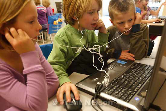 left to right: Madison White, Porter Templin and Joshua Apgood share headphones while editing video clips. Students at Dilworth Elementary are producing a short film about their teacher, Sharon Gallagher-Fishbaugh, who is one of five finalists for the NEA Foundation's Awards for Teaching Excellence. Students worked on the project Tuesday, November 3 2009.