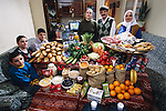 (MODEL RELEASED IMAGE). The Çelik family in the main room of their three-room apartment in Istanbul, Turkey, with a week's worth of food. Mêhmêt Çelik, 40, stands between his wife Melahat, 33 (in black), and her mother, Habibe Fatma Kose, 51. Sitting on the couch are their children (back to front) Mêtin, 16, Semra, 15, and Aykut, 8. Cooking method: gas stove. Food preservation: refrigerator-freezer. /// The Çelik family is one of the thirty families featured in the book Hungry Planet: What the World Eats (p. 252). Food expenditure for one week: $145.88 USD. (Please refer to Hungry Planet book p. 253 for the family's detailed food list.)