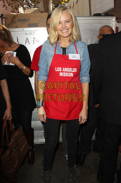 Malin Akerman.Los Angeles Mission Thanksgiving Dinner 2012 held at the LA Mission, Los Angeles, California, USA..November 21st, 2012.full length red apron blue gloves smiling shirt black jeans denim .CAP/ADM/KB.©Kevan Brooks/AdMedia/Capital Pictures.