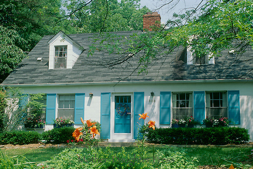 White Cape Cod style house, Blue Shutters, windowboxes and orange day lilies, Midwest USA