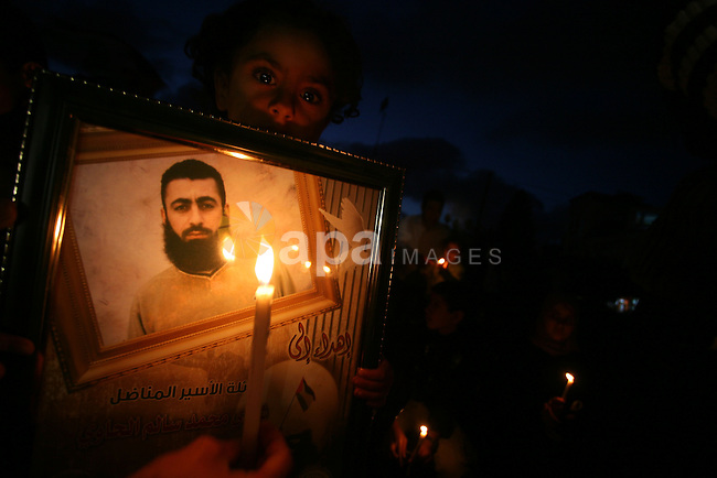 """Palestinian women and children stage a candlelight protest against the continuing Israeli blockade of the Gaza Strip on April 5, 2010 in Gaza City. Israel imposed strict closures on Gaza's borders after Israeli soldier Gilad Shalit was captured by Palestinian militants and tightened them when Hamas seized power in June 2007, sealing the territory of 1.5 million people off from all but vital humanitarian aid. Arabic writing on placard reads: """"Freedom for Gaza."""" Photo by Mohammed Othman"""