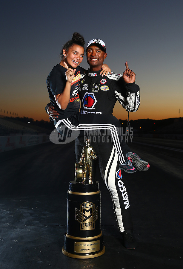 Nov 13, 2016; Pomona, CA, USA; NHRA top fuel driver Antron Brown (right) and daughter Arianna Brown pose for a portrait with the world championship trophy following the Auto Club Finals at Auto Club Raceway at Pomona. Mandatory Credit: Mark J. Rebilas-USA TODAY Sports