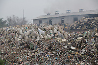 """A view of a junk yard where sacks of electronic trash await recycling in Nanyang. Each year, between 20 and 50 million tons of electronic waste is generated globally. Most of it winds up in the developing world.Some of the most popular destinations for dumping computer hardware include China, India, and Nigeria. It can be 10 times cheaper for a """"recycler"""" to ship waste to China than to dispose of it properly at home. With the market for e-waste expected to top $11 billion by 2009, it's lucrative to dump on the developing world."""