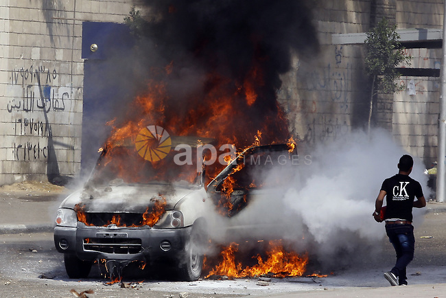 An Egyptian man tries to extinguish a police car set on fire by students of Al-Azhar University, who are supporters of the Muslim Brotherhood and deposed President Mohamed Mursi, during clashes with riot police at the university's campus in Cairo's Nasr City district, March 30, 2014. The Muslim Brotherhood, which had propelled Mursi to power at the ballot box, accuses the army of staging a coup against a legitimately chosen president and destroying democracy. The demonstration against former Defence Minister Field Marshal Abdel Fattah al-Sisi after Sisi announced that he will run for presidential elections. Photo by Mohammed Bendari