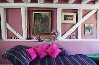 The walls of the living room are painted a strawberry pink with the timbers picked out in white to contrast