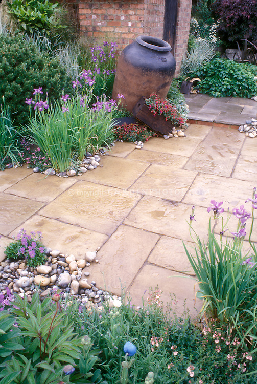 Stone patio with rustic urn, irises, spring flowering plants 3742