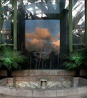 Tropical Rainforest Glasshouse (formerly Le Jardin d'Hiver), 1936, René Berger, Jardin des Plantes, Museum National d'Histoire Naturelle, Paris, France. Detail of a fountain surrounded by tree ferns, behind which a rectangular glass structure reflects the trees of the Jardin des Plantes beneath a cloudy late afternoon sky. The fountain is seen amongst luxuriant vegetation and the glass and metal structure of the Art Deco building.