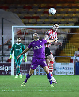 Lincoln City's Jason Shackell heads clear under pressure from  Carlisle United's Hallam Hope<br /> <br /> Photographer Andrew Vaughan/CameraSport<br /> <br /> The Emirates FA Cup Second Round - Lincoln City v Carlisle United - Saturday 1st December 2018 - Sincil Bank - Lincoln<br />  <br /> World Copyright © 2018 CameraSport. All rights reserved. 43 Linden Ave. Countesthorpe. Leicester. England. LE8 5PG - Tel: +44 (0) 116 277 4147 - admin@camerasport.com - www.camerasport.com
