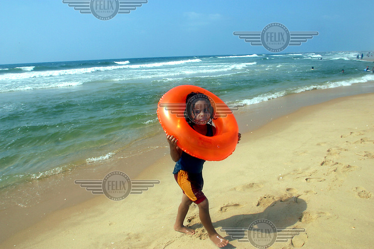 A Palestinian girl walks on the beach of Gaza city with a red inflatable ring around her head and shoulders..