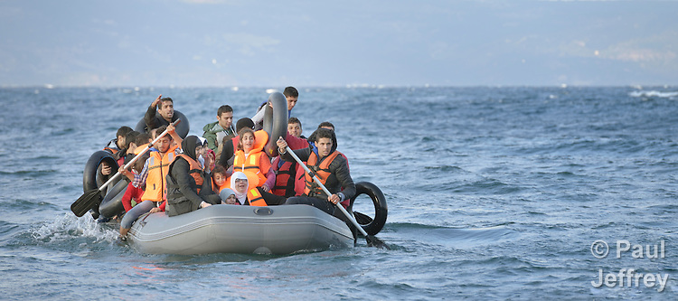 Refugees travel in a rubber boat across the Aegean Sea from Turkey to the Greek island of Lesbos on October 30, 2015.  They were received on a beach near Molyvos by local and international volunteers, then proceeded on their way toward western Europe. The boat was provided by Turkish traffickers to whom the refugees paid huge sums to arrive in Greece. Yet the motor quit during the crossing and the refugees were forced to paddle for several hours.
