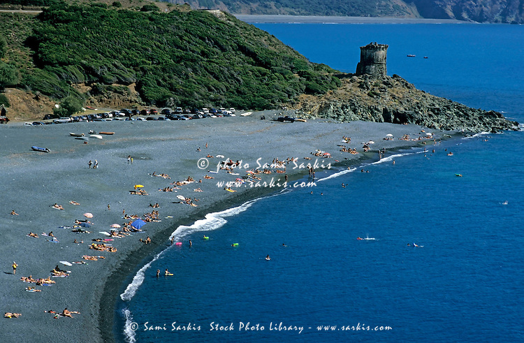 Sunbathers on a black sand beach, Cape Corse, Corsica, France.