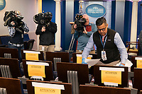 Fin Gomez, a board member of the White House Correspondent's Association, rearranges seating positions in the White House briefing room in Washington, DC on March 23, 2020 to affect social distancing in response to the spread of coronavirus.<br /> Credit: Chris Kleponis / Pool via CNP/AdMedia
