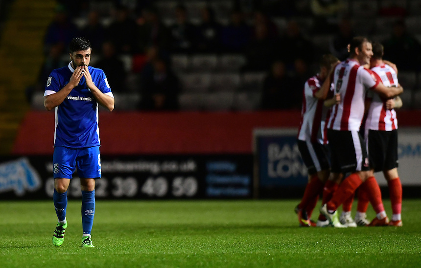 North Ferriby United's Curtis Bateson reacts as Lincoln City's Bradley Wood celebrates scoring his sides sixth goal with team-mates<br /> <br /> Photographer Chris Vaughan/CameraSport<br /> <br /> Football - Vanarama National League - Lincoln City v North Ferriby United - Tuesday 9th August 2016 - Sincil Bank - Lincoln<br /> <br /> &copy; CameraSport - 43 Linden Ave. Countesthorpe. Leicester. England. LE8 5PG - Tel: +44 (0) 116 277 4147 - admin@camerasport.com - www.camerasport.com