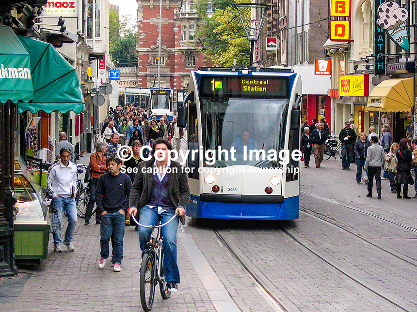 Holland, Netherlands, street scene, Amsterdam, cyclist, tram, 200710050085..Copyright Image from Victor Patterson, 54 Dorchester Park, Belfast, UK, BT9 6RJ..Tel: +44 28 9066 1296.Mob: +44 7802 353836.Voicemail +44 20 8816 7153.Skype: victorpattersonbelfast.Email: victorpatterson@mac.com.Email: victorpatterson@ireland.com (back-up)..IMPORTANT: If you wish to use this image or any other of my images please go to www.victorpatterson.com and click on the Terms & Conditions. Then contact me by email or phone with the reference number(s) of the image(s) concerned.