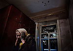 Avdiivka, eastern Ukraine, 2017.<br /> <br /> Valentina Fedorovna, 83, in one of the front rooms of her house, on the outskirts of Avdiivka, that was hit by shellfire.<br /> <br /> The house is on the frontline and has been badly damaged by heavy artillery shelling from pro-Russian separatists. <br /> <br /> A shell hit the front of her house on 23/5/17, smashing all the windows in the front, and spraying shrapnel into the rooms, but the house had already suffered damage from previous shelling and sniper fire.<br /> <br /> The sounds of explosions and gunfire can be heard every day, but she tries to carry on as normal, while receiving and giving support to the few elderly neighbours she has left.<br /> <br /> She has lived in the area all her life and moved to this house in the 1960&rsquo;s when she got married. <br /> <br /> Her children are constantly asking her to move in with them but she vows never to leave - <br /> &lsquo;I have been building my house for many years, how can I leave it alone&rsquo;.