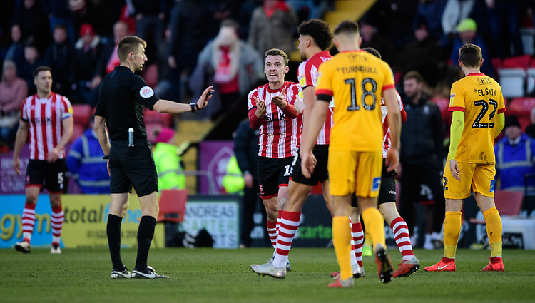 Lincoln City's Harry Toffolo unsuccessfully appeals for a penalty from Referee Michael Salisbury<br /> <br /> Photographer Chris Vaughan/CameraSport<br /> <br /> The EFL Sky Bet League Two - Lincoln City v Northampton Town - Saturday 9th February 2019 - Sincil Bank - Lincoln<br /> <br /> World Copyright © 2019 CameraSport. All rights reserved. 43 Linden Ave. Countesthorpe. Leicester. England. LE8 5PG - Tel: +44 (0) 116 277 4147 - admin@camerasport.com - www.camerasport.com