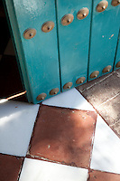 Detail of a green studded wooden door against a terracotta and white tiled floor