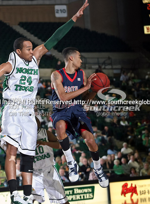 North Texas Mean Green forward Kedrick Hogans (24) defends South Alabama Jaguars guard/forward Gary Redus (2) during the NCAA  basketball game between the South Alabama Jaguars and the University of North Texas Mean Green at the North Texas Coliseum,the Super Pit, in Denton, Texas. UNT defeated South Alabama 82 to 79...