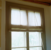 Sheer green-checked roller blinds across the windows of the dining room help to diffuse the light