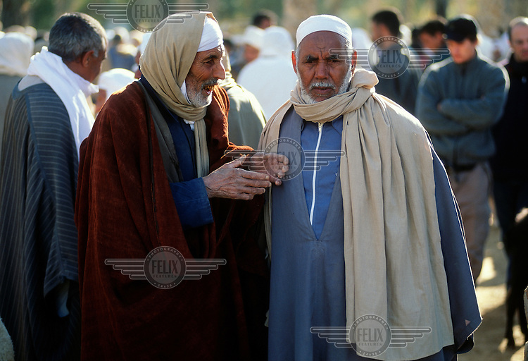 Elderly men in discussion at the weekly animal market at the oasis..