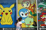 """May 9, 2010 - Tokyo, Japan - A young Japanese girl looks at a poster featuring video game Nintendo's Pokemon characters at the official Pokemon store in Tokyo on May 9, 2010. Nintendo recently announced that the DS handheld device had become the best selling gaming handheld of all time, with a total of 129 million units sold. The DS 'family' have surpassed the """"Game Boy"""" series which hit 118 million over two decades."""
