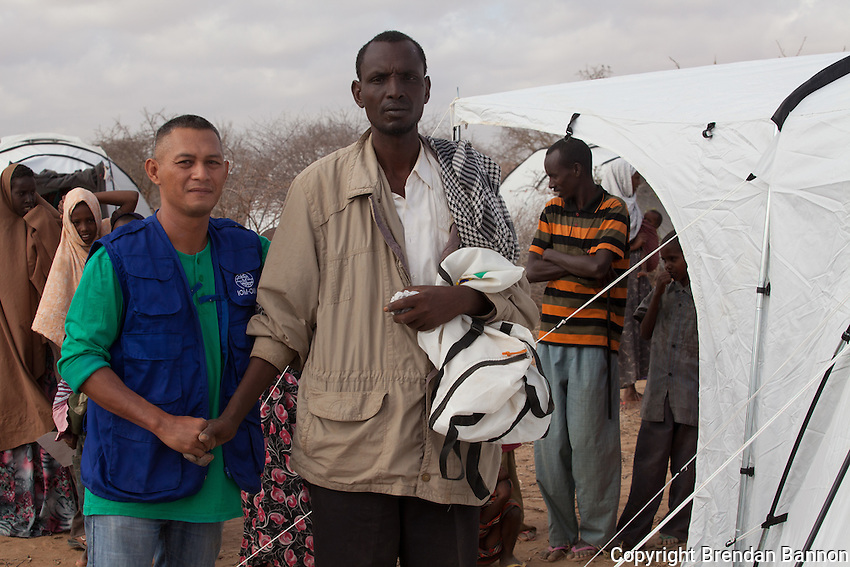 IOM workers assemble a tent for Ibrahim Salat Mohamed, a Somali refugee from Baidoa who ewas moved from Dagahaley outskirts to Ifo 2. He fled Somalia in June 2011 with his wife and 4 children because of drought and trouble with Al- Shabaab. September 2011.