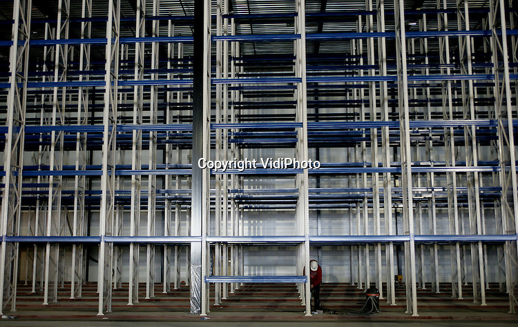 Foto: VidiPhoto..HETEREN - Langs de snelweg A50 bij Heteren wordt het grootste distributiecentrum van Kruidvat gebouwd. De enorme loods is 200 meter lang en 140 meter breed. Als de bouw in september gereed is, meet de totale vloeroppervlakte van Kruidvat bij Heteren 47.000 vierkante meter, exclusief 3500 vierkante meter kantoren en 4500 vierkante meter sorteerruimte. Bijzonder is dat de kantoorruimten aan het dak worden opgehangen. De ruwbouwkosten betalen 10 miljoen euro. De aankleding en inrichting minimaal driemaal zoveel. Hoofdaannemer is Gerritsen Bouwgroep BV uit Renkum. De gevelbeplating wordt aangebracht door Geertsen de Reuver uit Nieuwegein. Netcon uit Doetinchem verzorgt het stellingwerk.