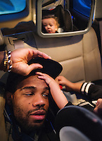 Olympic Gold champion wrestler Jordan Burroughs (cq) with his son Beacon Burroughs (cq, age 19 months) on the road driving to Sidney, Nebraska for a guest appearance at a wrestling duel, Saturday, February 13, 2015. Burroughs has become a celebrity in the wrestling world due to his success on the mat.<br /> <br /> Photo by Matt Nager