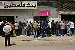Palestinians of Social Affairs wait in front of Bank of Palestine to withdrew their financial aid in Gaza City on April 11, 2017. Photo by Ashraf Amra