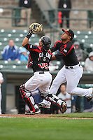 Catcher Juan Centeno (59) and third baseman Heiker Meneses (9) of the Rochester Red Wings collide on a popup against the Scranton Wilkes-Barre Railriders on May 1, 2016 at Frontier Field in Rochester, New York. Red Wings won 1-0.  (Christopher Cecere/Four Seam Images)