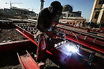 A welder arc welds brackets onto structural I-beams at a construction site in central Suleymaniah, Iraqi Kurdistan on Tues. Sept. 19, 2006. The construction site, which has as its neighbors, in the background, a new cultural arts center and theatre and a new mosque, both under construction, contains a dozen multi-story high end apartment buildings, all financed by Iranian investors.