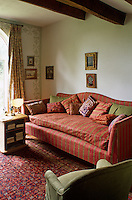 A large sofa covered in a green and red stripe dominates this small sitting room