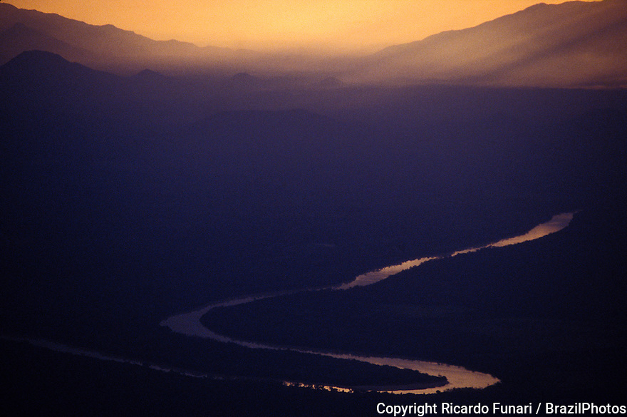 River curves in Amazon rain forest, Brazil - aerial view of valley at dusk, dense forest in fog.