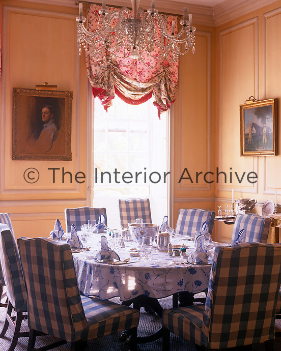 This pink panelled dining room features checked slip covers on the dining chairs and a table laid with a blue and white floral cloth
