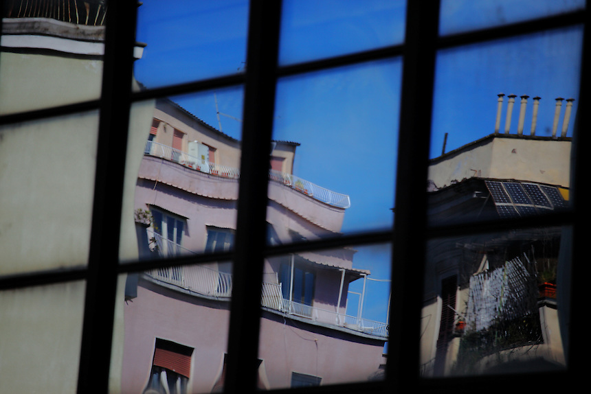 A reflected image captured between the mirror glass walls of a group of modern buildings surrounded by old ones in via Morgagni in Rome. There is in particular a distorted terrace angle and a series of smokestacks. Digitally Improved Photo.