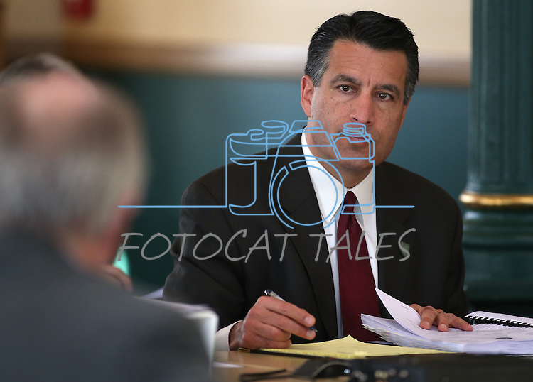 Nevada Gov. Brian Sandoval works in a meeting of the Board of State Prison Commissioners at the Capitol in Carson City, Nev., on Tuesday, March 19, 2013..Photo by Cathleen Allison
