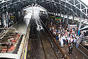 Mumbai, India<br /> Bandra station in the pouring rain where hundreds of commuters pack onto the station platform to rerun home after work. There is a a mad scramble for limited space on the trains and many are left hanging on the sides of the train or leaning out of the open doors.<br /> <br /> Picture by Gavin Rodgers/ Pixel8000<br />  07917221968