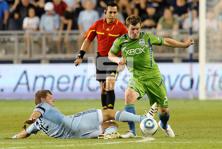 Luke Sassano (32) midfielder Sporting KC slide tackles Mike Fucito (2) forward Seattle Sounders..... Sporting Kansas City were defeated 1-2 by Seattle Sounders at LIVESTRONG Sporting Park, Kansas City, Kansas.
