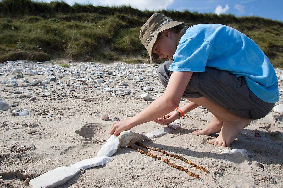 Naturkunst am Strand, Mädchen, Kind baut aus Steinen eine kleine Brücke, Steinbrücke, Strandkunst, Strandgut, Strand, Meer, Küste