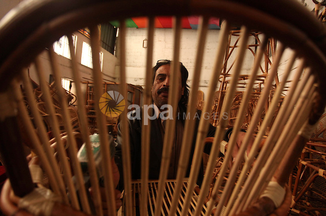 A Palestinian man works on bamboo furniture at his workshop in Gaza city on April 16, 2015. Bamboo is a product of southeast Asian countries and before the Israeli blockade of the Gaza Strip, Gaza traders used to bring it in to the coastal territory in adequate quantities to allow the industry to remain viable. The traditional industry fade away gradually due to economic instability in the region and the lack of training for the industry across the Gaza Strip. Photo by Ashraf Amra