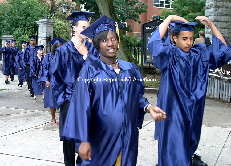 WATERBURY- JUNE 17- 061711DA03-Graduate of Enlightenment School in Waterbury, Ricardo Andujar takes a hold of his graduation cap as he walks along side of LaShayla Yon before graduation ceremonies that were held at the Mattatuck Museum in Waterbury on Friday.