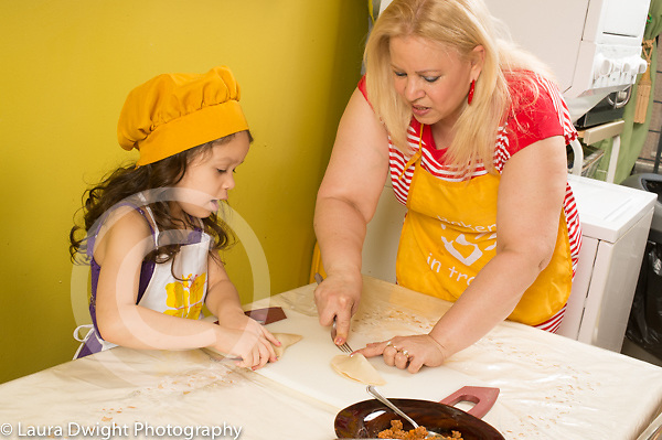 5 year old girl in kitchen with grandmother learning how to make empanadas