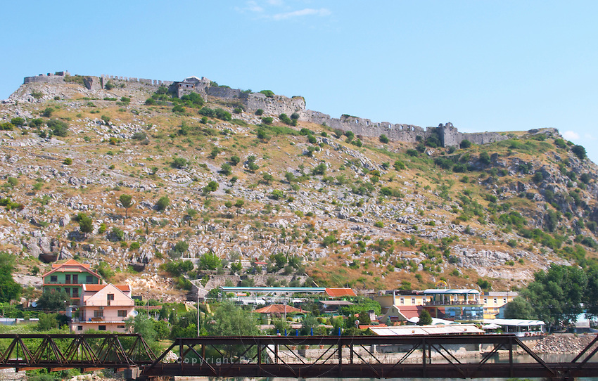 The Rozafa hilltop castle fortress fort between Shkodra and Lezhe. In the foreground an old iron railway bridge crossing the river. Albania, Balkan, Europe.