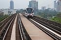 RapidKL train on elevated railway with Kuala Lumpur in background. Kuala Lumpur, Selangor, Malaysia