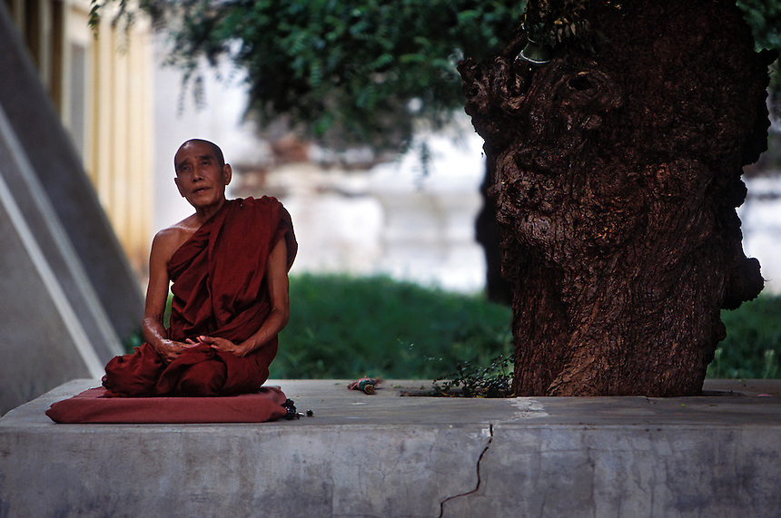 A monk meditates in the Shwezigon Pagoda, a place said to contain the remains of the Buddha, Bagan, Burma, 2006.