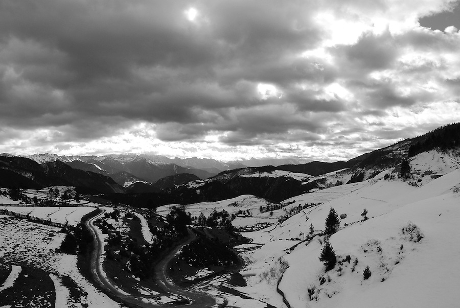 Magnificent mountainside view of China nature landscape in black and white photography. The mountains are covered in snow with heavy thick cloud.