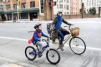 New York, New York City, during the time of Coronavirus. Super boy goes out for a bike ride on Easter.