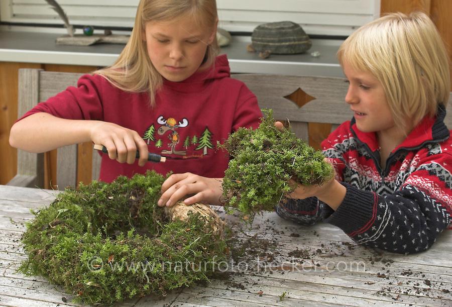 Kinder basteln einen Lichterkranz für die Adventszeit, Adventskranz, Kinder binden Moos mit Draht auf einen Unterkranz aus Stroh
