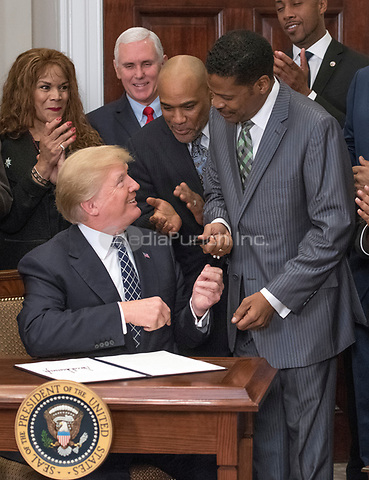United States President Donald J. Trump hands the pen he used to sign the document to Isaac Newton Farris, Jr., Nephew of Martin Luther King Jr., after signing the proclamation to honor Dr. Martin Luther King, Jr. Day in the Roosevelt Room of the White House in Washington, DC on Friday, January 12, 2018.<br /> Credit: Ron Sachs / CNP /MediaPunch